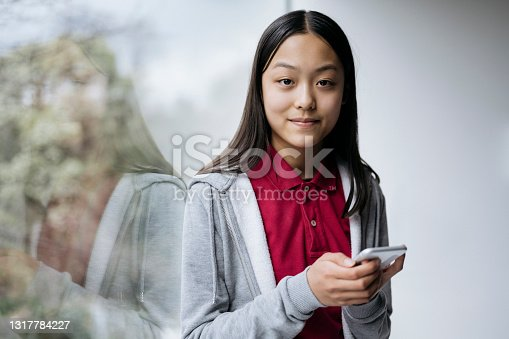 Close-up of 13 year old girl with long black hair in casual clothing standing next to picture window and pausing from using mobile device to smile at camera.