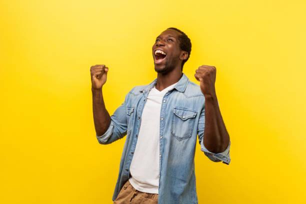 Portrait of ecstatic overjoyed handsome man expressing winning gesture. indoor studio shot isolated on yellow background Portrait of ecstatic overjoyed handsome man in denim casual shirt expressing winning gesture with raised fists and screaming, celebrating victory. indoor studio shot isolated on yellow background cheering stock pictures, royalty-free photos & images