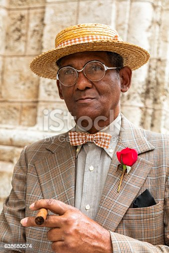 Portrait of an elegant, dark, elderly Cuban gentleman in a suit, straw boater hat, and a cigar standing in front of a wall in Havana, Cuba, 48 megapixel image.