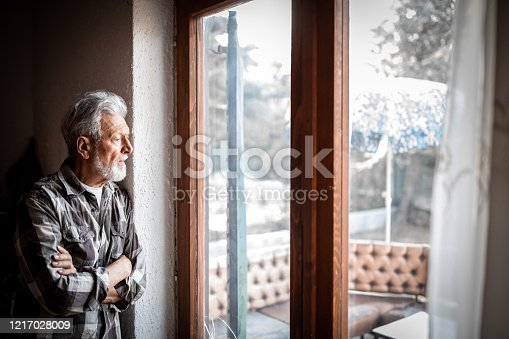 Sad Mature man Suffering From Agoraphobia Looking Out Of Window