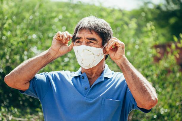 Porträt eines älteren Mannes, der eine selbstgemachte Schutzmaske trägt, die während der Quarantäne sonnen. Coronavirus, Covid-19 und Pandemie-Konzept – Foto