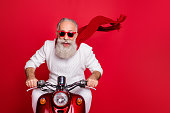istock Portrait of elderly modern person in eyewear eyeglasses driving his bike wearing white sweater isolated over red background 1179765094