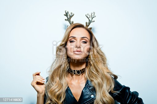 Beautiful young woman wearing leather jacket and reindeer horns standing against grey background and looking at camera.