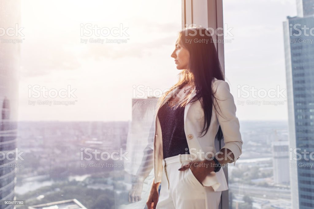 Portrait of elegant business lady wearing white formal suit standing near window looking at cityscape stock photo