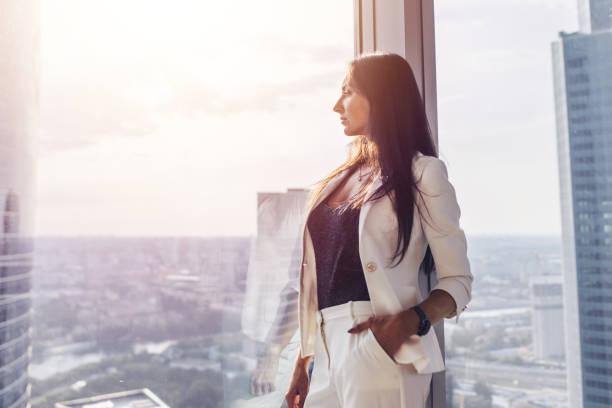 도시 풍경 보고 창 근처 흰색 정식 소송 서 입고 우아한 비즈니스 여자의 초상화 - 풍경보기 뉴스 사진 이미지