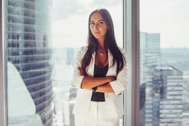 Portrait of elegant business lady wearing white formal suit standing near window looking at camera stock photo
