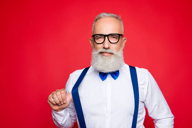 portrait of elegant, confident macho, old barber, stylist draw off suspender with thumb finger, looking at camera with simper, isolated on red background - arrogance stock pictures, royalty-free photos & images