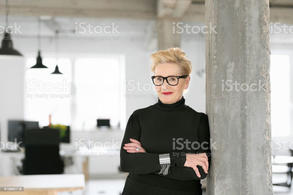 Portrait of elegant senior businesswoman in the modern studio Portrait of elegant senior businesswoman standing in the modern studio, smiling at the camera. 60-69 Years Stock Photo