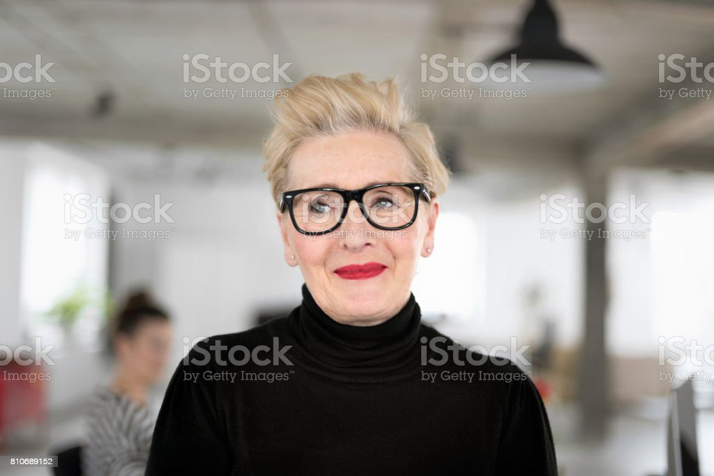 Portrait of elegant senior businesswoman in the studio Portrait of smiling elegant senior businesswoman standing in her office. Close up of face. 60-69 Years Stock Photo