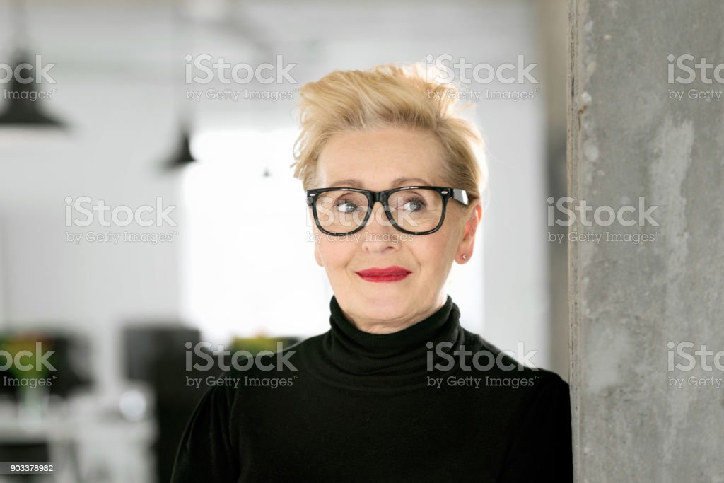 Portrait of elegant senior businesswoman in the studio Portrait of elegant senior businesswoman standing in her office. Close up of face. 60-69 Years Stock Photo