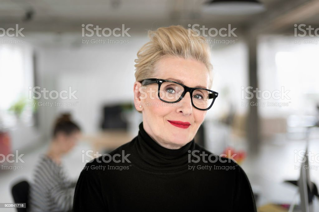 Portrait of elegant senior businesswoman in the studio Portrait of elegant senior businesswoman standing in her office, smiling at the camera. Close up of face. 60-69 Years Stock Photo