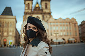 Hello november. Portrait of elegant middle aged woman in beige trench coat and black beret with black mask at Old Town Square in Prague.