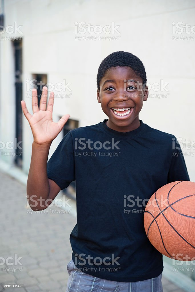 Portrait of elementary age school boy holding a ball. stock photo