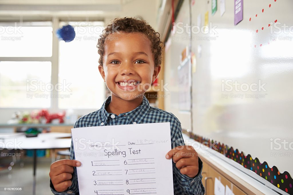 Portrait of elementary school boy holding up his test paper stock photo