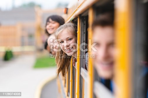 A group of elementary students sitting on a school bus stick their heads out the window and smile at the camera. The focus is on a girl with braces.