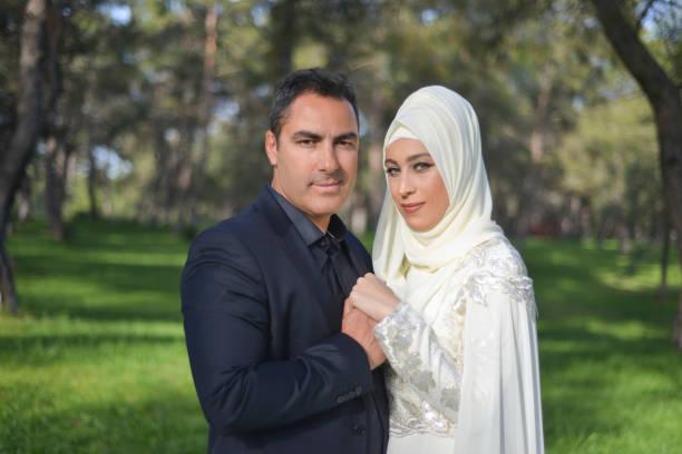 verticale de couples musulmans embrassés de mariée et de marié regardant l'appareil-photo en retenant les mains de l'un l'autre dans un parc public - mariage musulman photos et images de collection