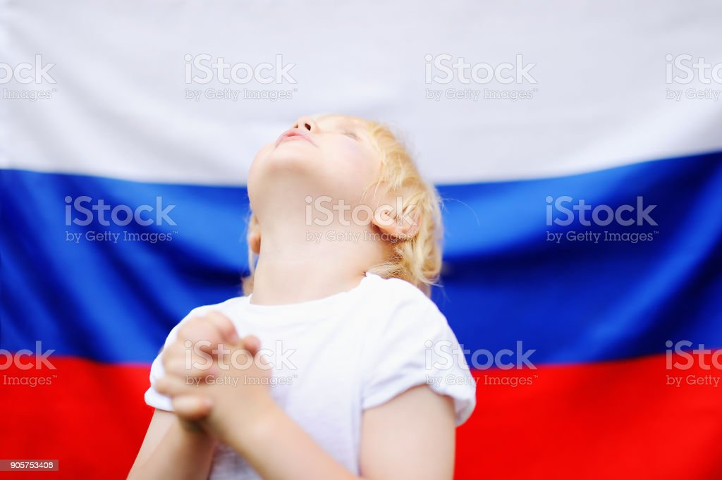 Portrait of emotional little boy with russian flag on background stock photo
