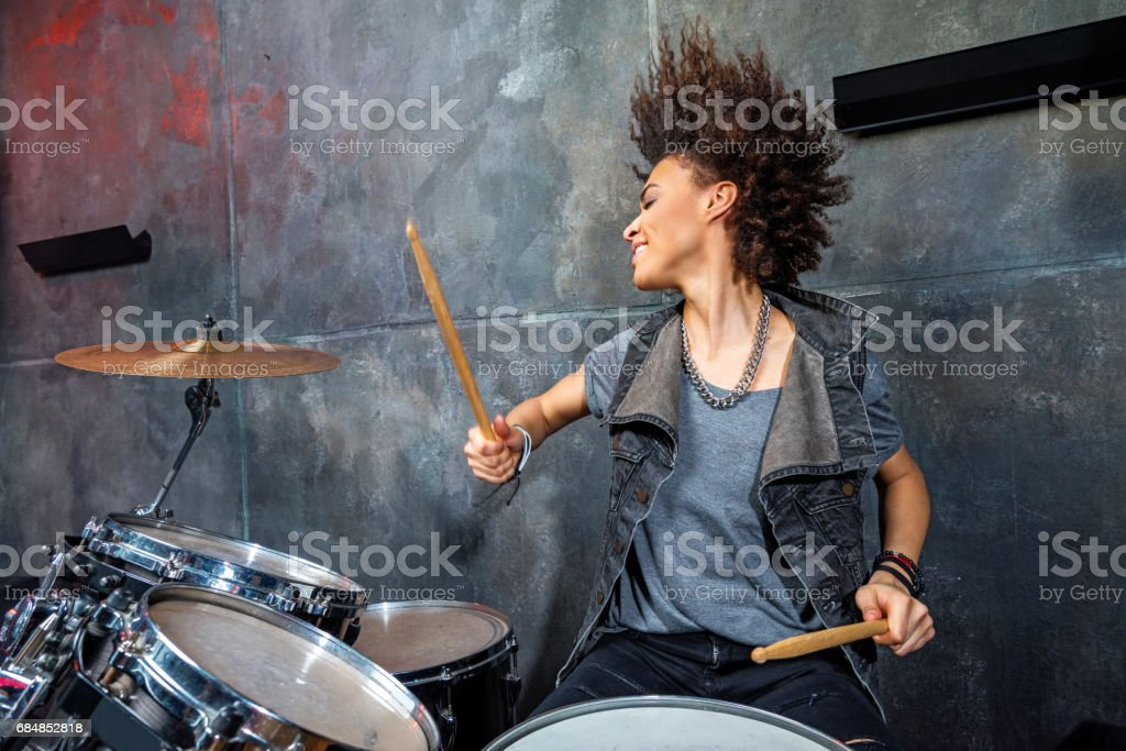 portrait of emotional woman playing drums in studio, drummer rock concept - foto de acervo