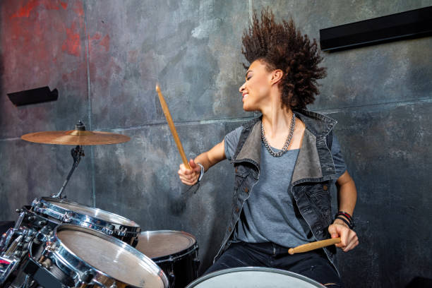 portrait of emotional woman playing drums in studio, drummer rock concept stock photo