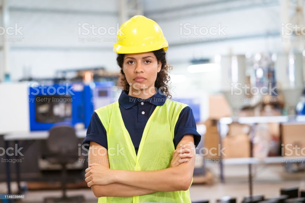 Portrait of engineer in hardhat with arms crossed Portrait of female apprentice wearing hardhat. Mid adult engineer is standing with arms crossed. She is in reflective clothing at factory. 30-34 Years Stock Photo