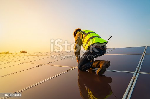 Portrait of engineer man or worker, people, with solar panels or solar cells on the roof in farm. Power plant with green field, renewable energy source in Thailand. Eco technology for electric power.