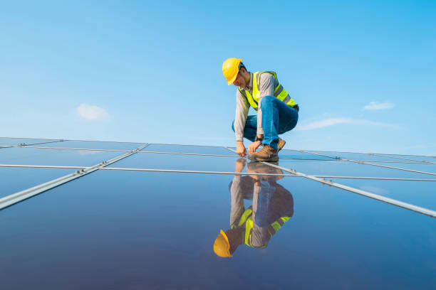 Portrait of engineer man or worker, people, with solar panels or solar cells on the roof in farm. Power plant with green field, renewable energy source in Thailand. Eco technology for electric power. stock photo