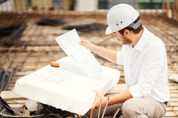 portrait of engineer reading plans on construction site stock photo