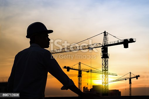 istock portrait of engineer silhouette wear a helmet at construction site with crane background and sunset 896712608
