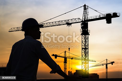 istock portrait of engineer silhouette wear a helmet at construction site with crane background and sunset 908895028