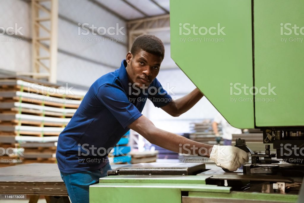 Portrait of engineer using puller machine Portrait of engineer using puller machine. Male young apprentice is wearing uniform. He is working in manufacturing industry. 25-29 Years Stock Photo
