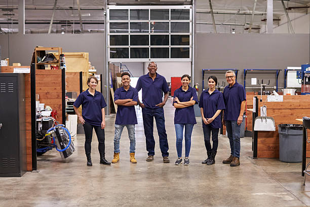 Portrait Of Engineers And Apprentices In Busy Factory stock photo