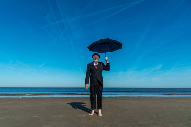 Portrait of Englishman with bowler hat and umbrella stands barefoot on the beach Looking at the camera.