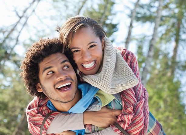 Portrait of enthusiastic couple piggybacking stock photo
