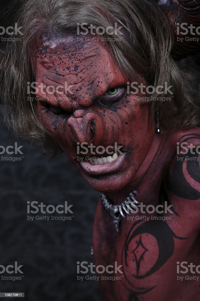 Portrait of Evil Demon in Red and Black Body Paint royalty-free stock photo