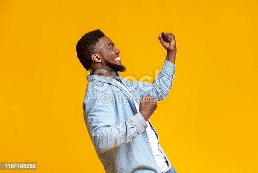 istock Portrait of excited african guy celebrating success with clenched fists 1184188388