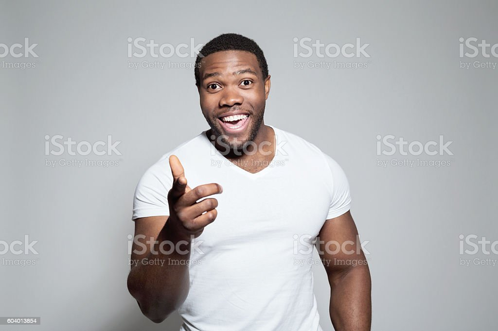 Portrait of excited afro american young man Portrait of excited afro american young man wearing white t-shirt, standing against grey background, pointing at camera with index finger. Adult Stock Photo