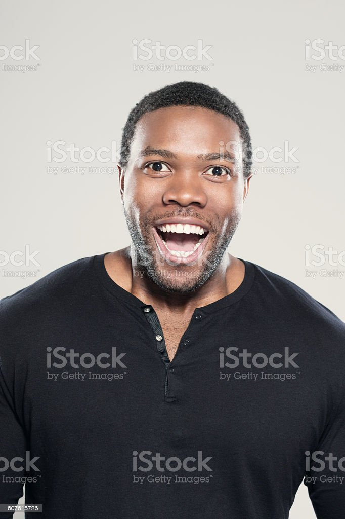 Portrait of excited afro american young man Portrait of excited afro american young man wearing black t-shirt, standing against grey background, laughing at camera. Adult Stock Photo