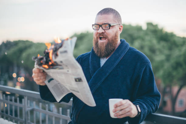 Portrait of excited (shocked) bearded man looking to the newspaper (on fire) - burning magazine in man's hands - hot and breaking news concept