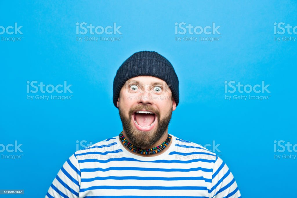 Portrait of excited bearded sailor screaming Portrait of excited bearded man wearing striped t-shirt and beanie hat screaming at camera. Studio shot, blue background. 30-34 Years Stock Photo