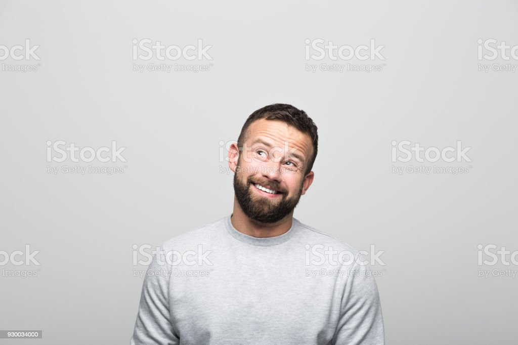 Portrait of excited bearded young man looking up at copy space Portrait of happy bearded young man looking up at copy space. Studio shot, grey background. 30-34 Years Stock Photo
