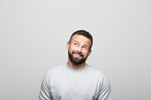 Portrait Of Excited Bearded Young Man Looking Up At Copy Space Stock Photo - Download Image Now