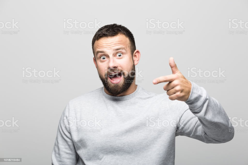 Portrait of excited bearded young man pointing with index finger Portrait of happy bearded young man pointing with index finger at the camera. Studio shot, grey background. 30-34 Years Stock Photo