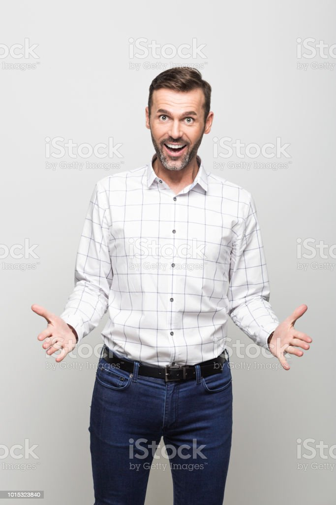 Portrait of excited businessman laughing at camera, grey background Portrait of handsome successful businessman wearing white shirt and jeans, smiling at the camera. Studio portrait, grey background. 30-39 Years Stock Photo