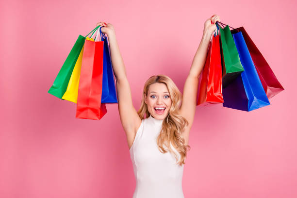 Portrait of excited cheerful girlfriend, positive glad chick having many colorful packets with gifts presents in hands up, yelling, isolated on pink background stock photo