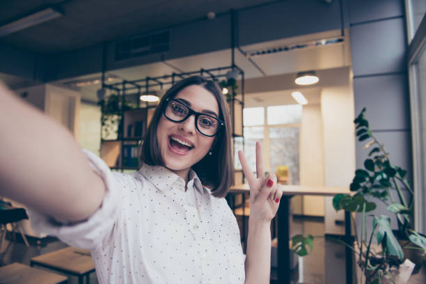 portrait of excited cheerful smiling young pretty woman in spectacles making selfie photo and showing v-sign with two fingers - selfie foto e immagini stock