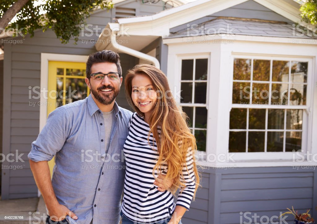 Portrait Of Excited Couple Standing Outside New Home stock photo