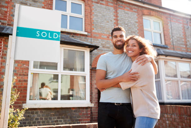 Portrait Of Excited Couple Standing Outside New Home With Sold Sign Portrait Of Excited Couple Standing Outside New Home With Sold Sign home ownership stock pictures, royalty-free photos & images