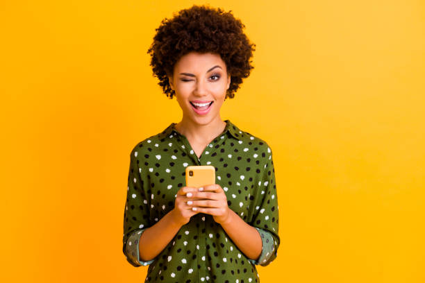 Portrait of excited crazy afro american girl hold smart phone use read social network news wear stylish green bright clothing isolated over yellow color background Portrait of excited crazy afro american girl hold smart phone use read social network, news wear stylish green bright clothing isolated over yellow color background blinking stock pictures, royalty-free photos & images