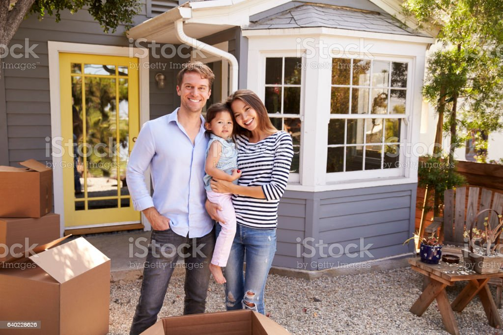 Portrait Of Excited Family Standing Outside New Home Portrait Of Excited Family Standing Outside New Home 2-3 Years Stock Photo