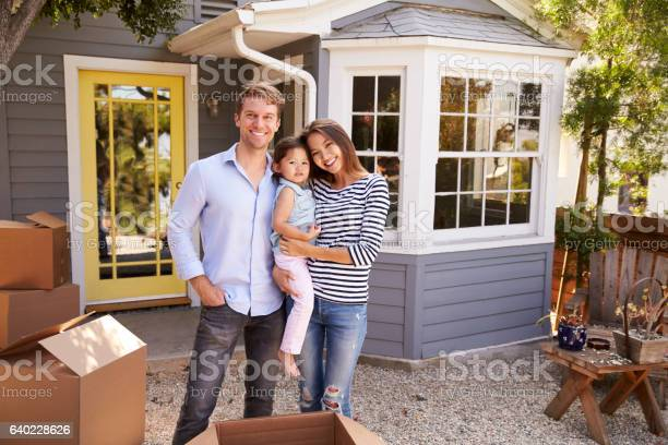 Portrait Of Excited Family Standing Outside New Home Stock Photo - Download Image Now